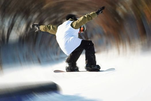 a snowboarder gets air and the background is radial blured