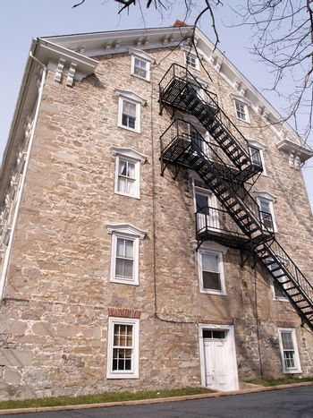 a black outside fire escape for an old stone building