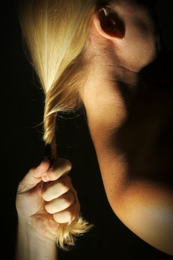 Abstract dramatically lit image of woman's shoulder, back and blond hair with male hand gripping her lock.