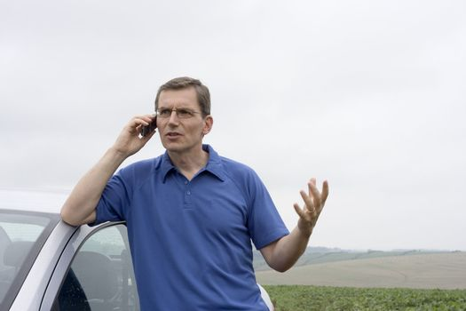 Angry man talking on cell phone beside a car