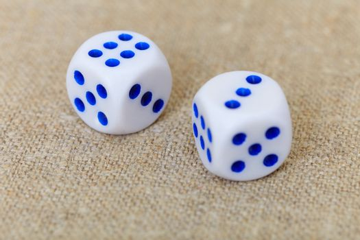 Two dice on coarse linen
