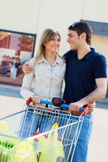 portrait of young couple pushing shopping cart outdoors