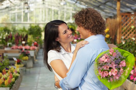 couple hugging in flower nursery