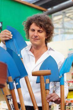 portrait of man choosing shovel in garden center