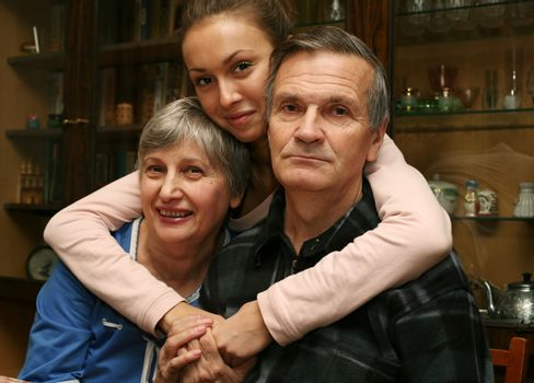 The grand daughter embraces the grandmother and the grandfather