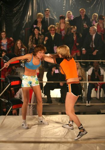 Two girls box on a ring on a background of spectators
