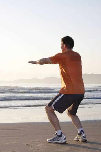 Jogger doing squat on a beach