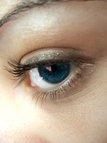 A macro shot of a pretty woman's blue eye and lashes - shallow depth of field.