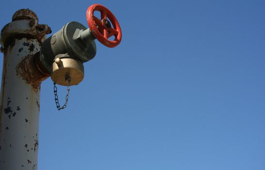 A water release valve on a clear blue sky with plenty of copy space.
