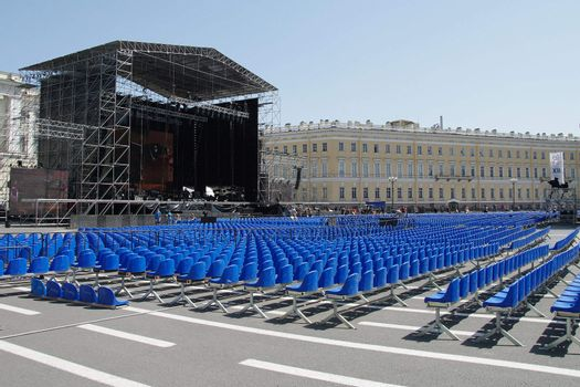 Rows of empty blue plastic chairs before the concert