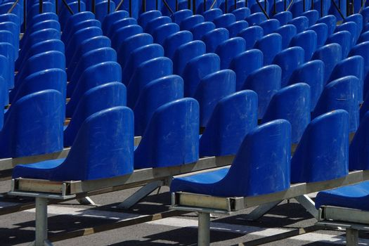 Rows of empty blue plastic chairs