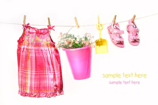 Little girl clothes and toys on a clothesline