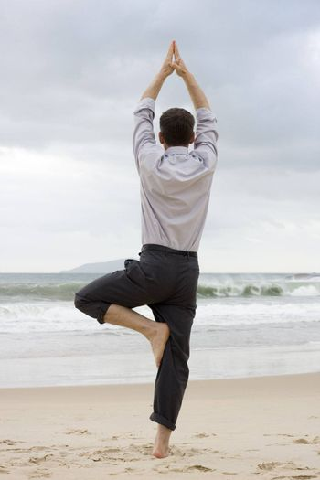 Businessman doing relaxation exercises on a beach