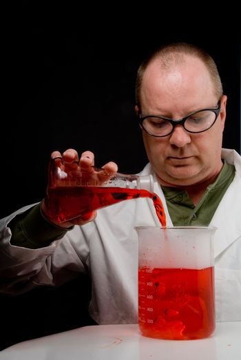 A Scientist pouring a solution into a beaker.