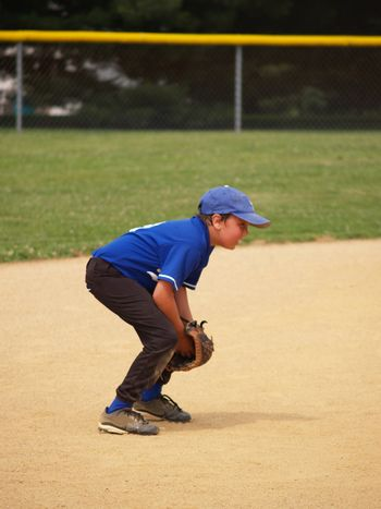 side view of a little league baseball player in the infield