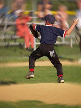 little league baseball pitcher with a blur