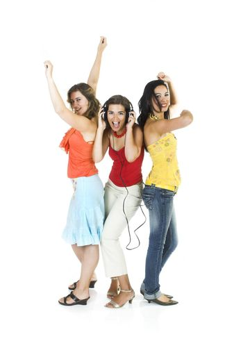 Three happy girls isolated on white dancing