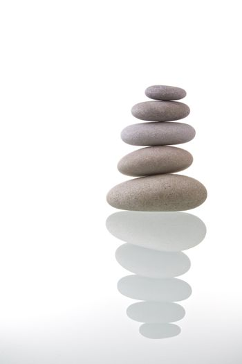 Pyramid of stacked pebble stones with reflection. Zen concept.