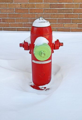 Red fire hydrant covered by snow