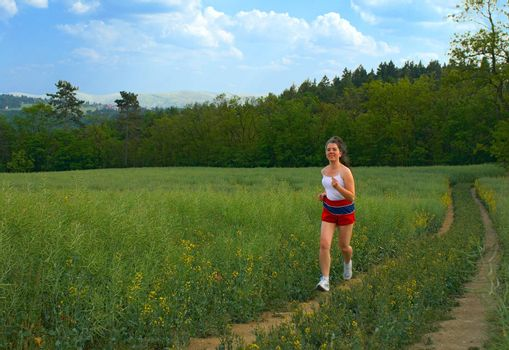 Day time training. The young woman runs on rural roads.