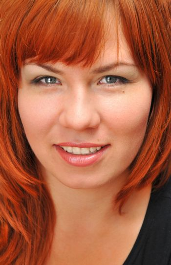 pretty young  girl with red hair is smiling
