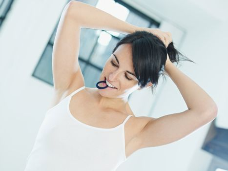 woman tying hair with rubber band in mouth