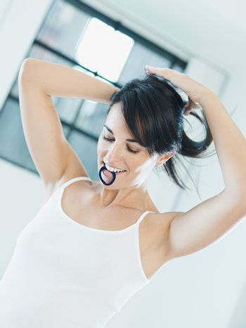 woman tieing hair with rubber band in mouth