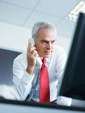 mature businessman on the phone in office