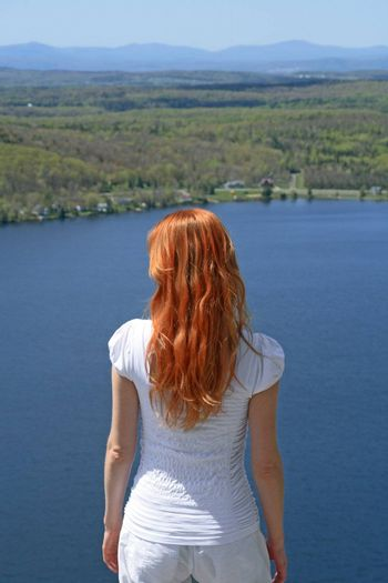Red-haired girl looking over blue lake from the mountain.
