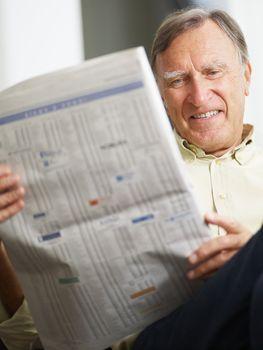 Senior man reading stock listings and smiling