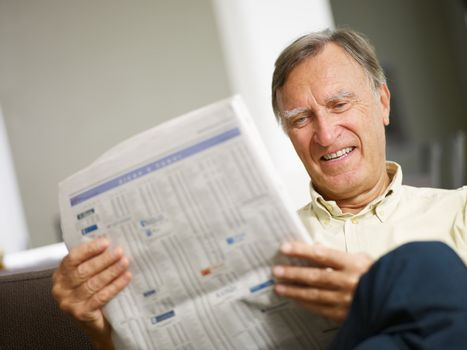 Senior man reading stock listings and smiling. Copy space