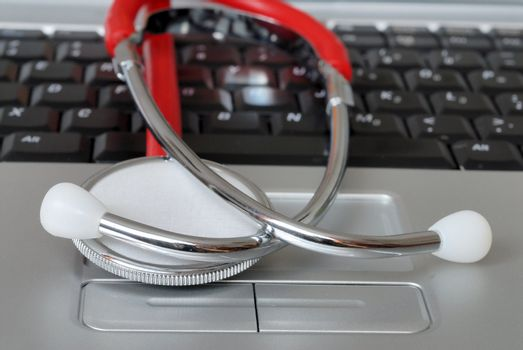 Macro of stethoscope lying on laptop keyboard