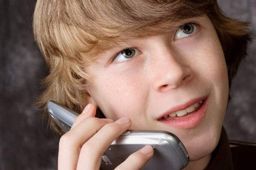 A teen boy speaks on a cell phone