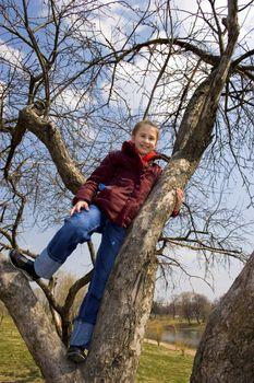 Girl will climb on tree. City park. Spring time.