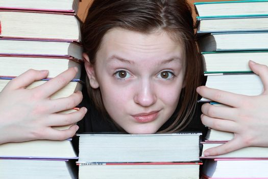 Portrait of nice young girl inside stacks of books