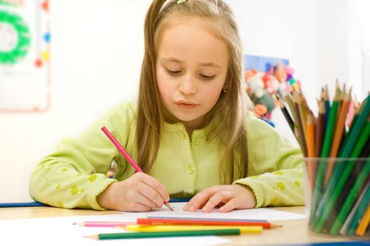 Pretty girl sitting and drawing with colored pencils