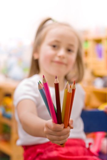 Little girl showing a few colored pencils [focus on pencils]