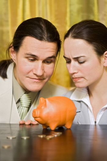 Young couple looking for money from a piggy bank
