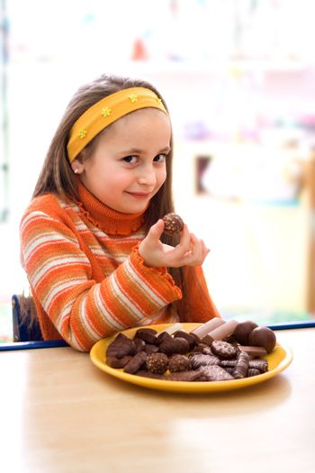 Pretty young girl taking a peace of chocolate from tray