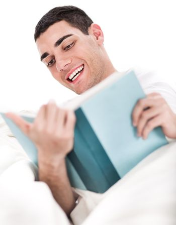 Young man enjoy reading book in bed over white background