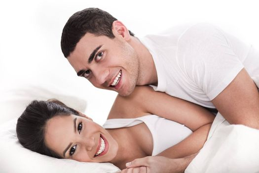 Young couple having fun in bed over white background