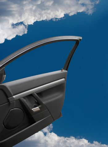 The open door of the car in the blue sky with clouds