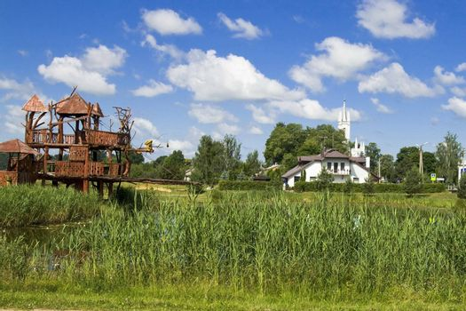 Park in the Lithuanian village. In the left party of lake - wooden abstraction - the house of monkeys, more to the right - a new rest house