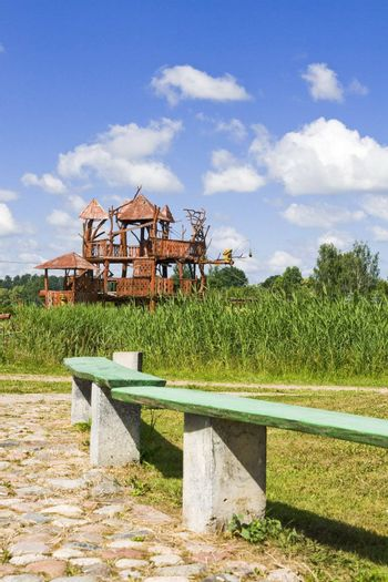 """Wooden bench at the park in Lithuania village. In the second plan a celebrity of park - the """"house of monkeys"""""""