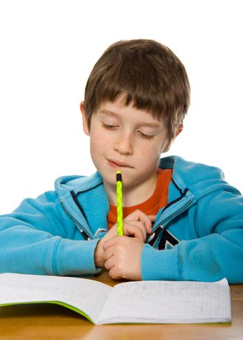 Young boy frowning over his homework, against a white background