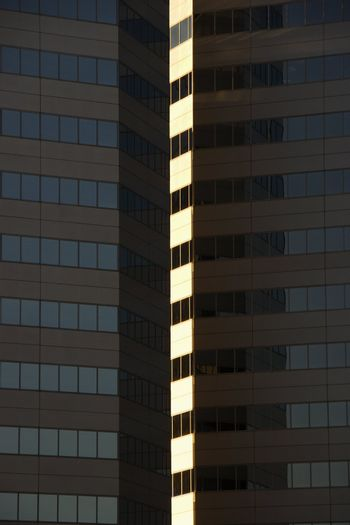 Side exterior of urban skyscraper building with light reflecting off windows.