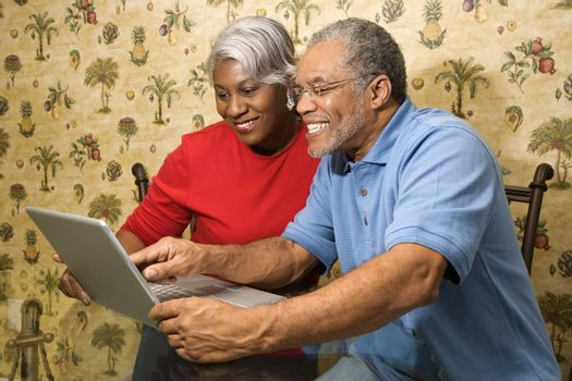 Portrait of mature African American couple looking and smiling at laptop in home.