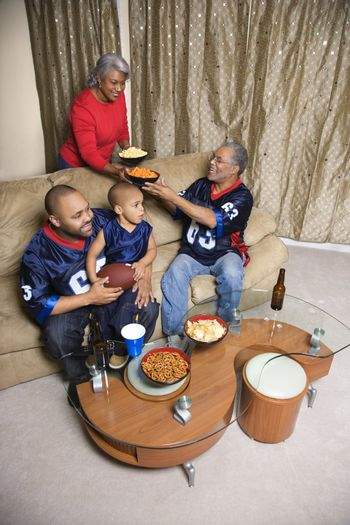 Mother serving snacks to male African-American family members during football game.