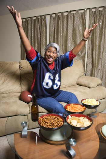 Portrait of a Middle-aged African-American woman wearing a football jersey with hands in the air watching football game.