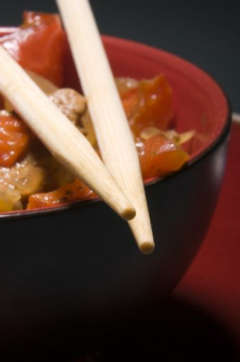 Red bowl with meat and vegetables and chopsticks